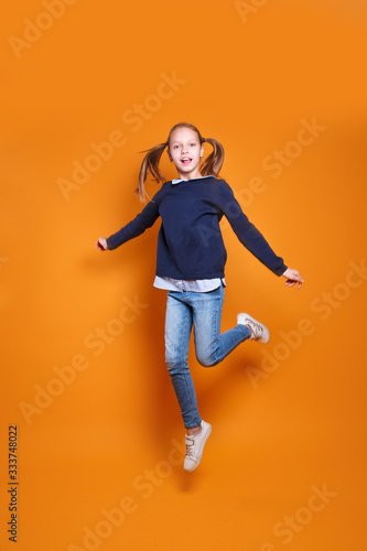 Fototapety, obrazy: funny little girl in casual clothes jumping on yellow background