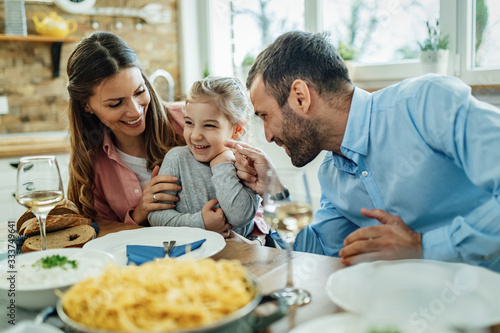 Cheerful family having fun during lunch at dining table. Fototapeta
