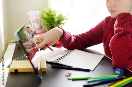 Valokuvatapetti Preteen schoolgirl doing her homework with digital tablet at home