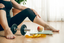 Sportive Woman Sitting On The Floor At Home After Weight Training, With A Digital Scale, An Apple And A Measuring Tape