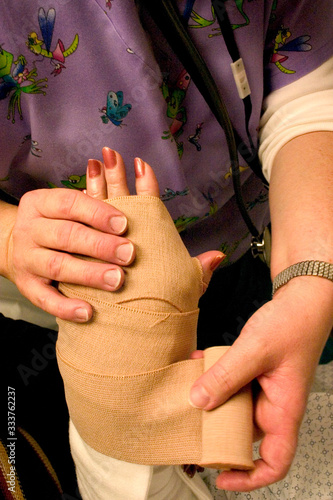 Photo Emergency room nurse wrapping temporary elastic bandage on broken wrist