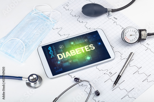 Tablet pc and medical stuff with DIABETES inscription, prevention concept