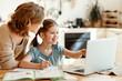 Leinwandbild Motiv Happy girl with mother studying online at home.