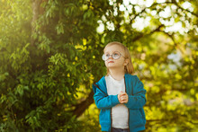 Little Blond Boy With Long Hair In Round Glasses On A Background Of Greens Looks Up