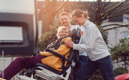 Photographie Two helpers picking up disabled senior woman for transport