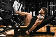 Athletic man trains legs on the simulator in the gym with weight. Athletic body, healthy lifestyle, fitness motivation, body positive.