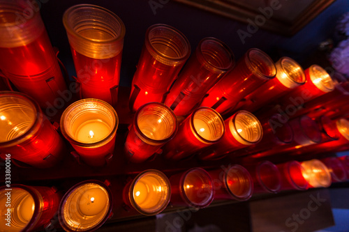 Red prayer candles lit in rows catholic church