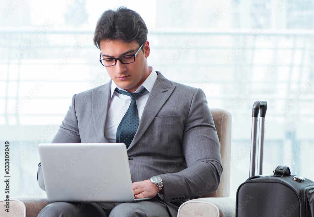 Fototapeta Young businessman in airport business lounge waiting for flight