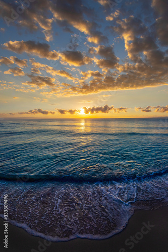 Obraz Beautiful sunrise cloudscape over the sea with waves lapping the beach - fototapety do salonu