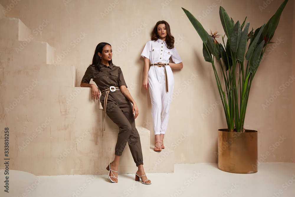 Fototapeta Two beautiful woman fashion model brunette hair friends wear overalls suit casual style sandals high heels accessory clothes safari Sahara journey summer hot collection plant flowerpot wall stairs.