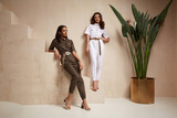 Fototapeta Fototapety na drzwi - Two beautiful woman fashion model brunette hair friends wear overalls suit casual style sandals high heels accessory clothes safari Sahara journey summer hot collection plant flowerpot wall stairs.