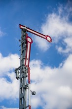 Old German Semaphore Railway Signal Against A Cloudy Blue Sky