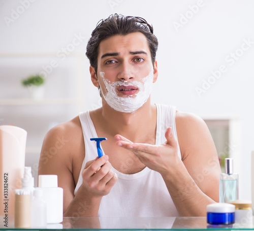 Photo Young handsome man shaving early in the morning at home