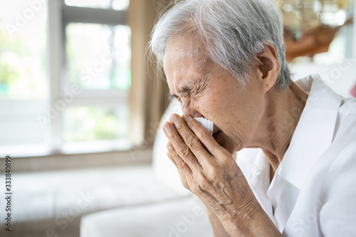 Fotografia, Obraz Sick asian senior woman blowing nose with tissue paper while runny nose,sneeze,e