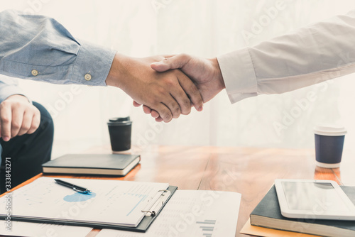 Business Meeting agreement Handshake concept, Hand holding after finishing up dealing project or bargain success at negotiation over office background Wallpaper Mural