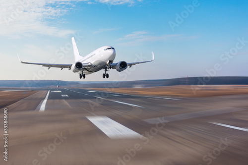 Obraz Runway at the airport and the plane flies and landing. - fototapety do salonu