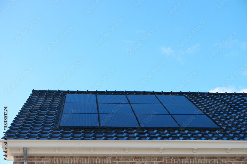 Fototapeta Newly build house in the Netherlands with solar panels attached on the roof against a sunny sky Close up of new building black solar panels