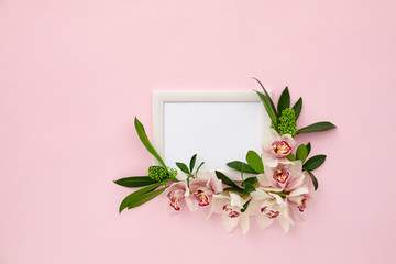 photo frame decorated with green leaves and orchid flowers on pink pastel background. empty space for text. mock up with copy space. Flat lay