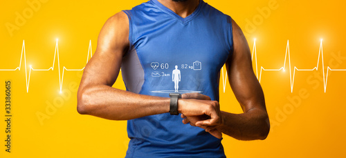 Photo Muscular afro guy looking at smart watch