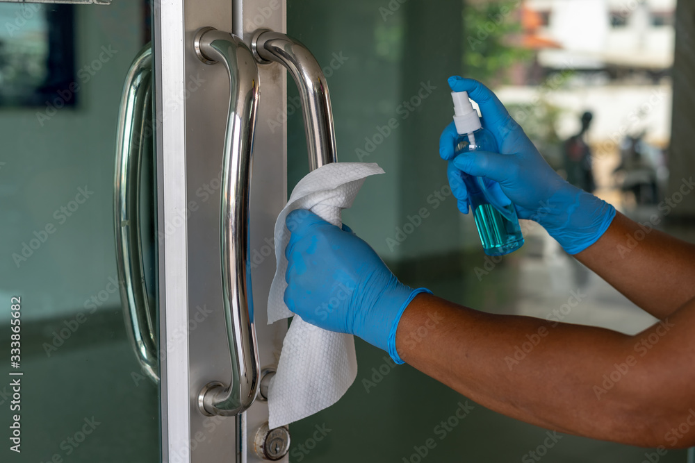 Fototapeta Close up of female hand using wet wipe and anti-sacterial sanitizer spray to clean the door handle before touch and open the door.Antiseptic,disinfection ,cleanliness and heathcare, anti virus concept