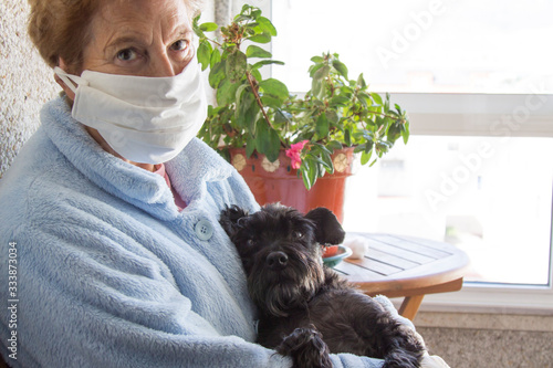 Obraz Portrait of senior woman with disposable medical mask and her dog. Safety in public places during the coronavirus outbreak. - fototapety do salonu
