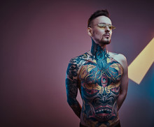 Self-assured Male Model Posing In A Neon Studio With A Half-naked Body Wearing Yellow Sunglasses And Inked In A Japanese Irezumi Style, Looking Stylish And Calm