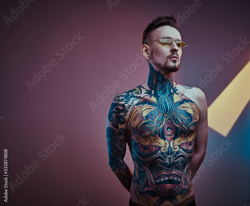 Self-assured male model posing in a neon studio with a half-naked body wearing yellow sunglasses and inked in a japanese irezumi style, looking stylish and calm Wall mural