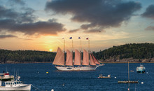 A Four Masted Schooner Touring Sightseers Through A Blue Harbor Off Bar Harbor, Maine