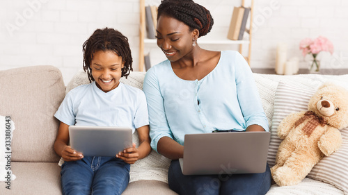 Afro mom and daughter using laptop and tablet
