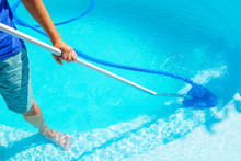 Swimming Pool Cleaning. A Man Is Cleaning The Pool. Service Care