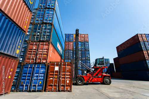 Foto Forklift truck handling cargo shipping container box in logistic shipping  container yard
