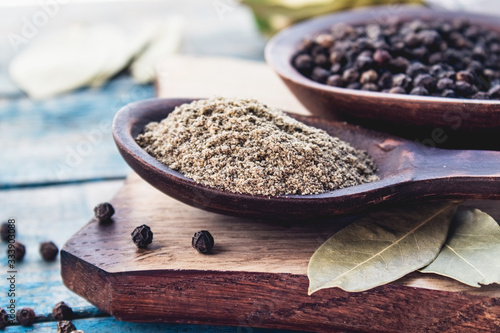 Leinwand Poster Ground black pepper in a spoon lies on a cutting board near the bay leaf and black pepper on a background of blue boards