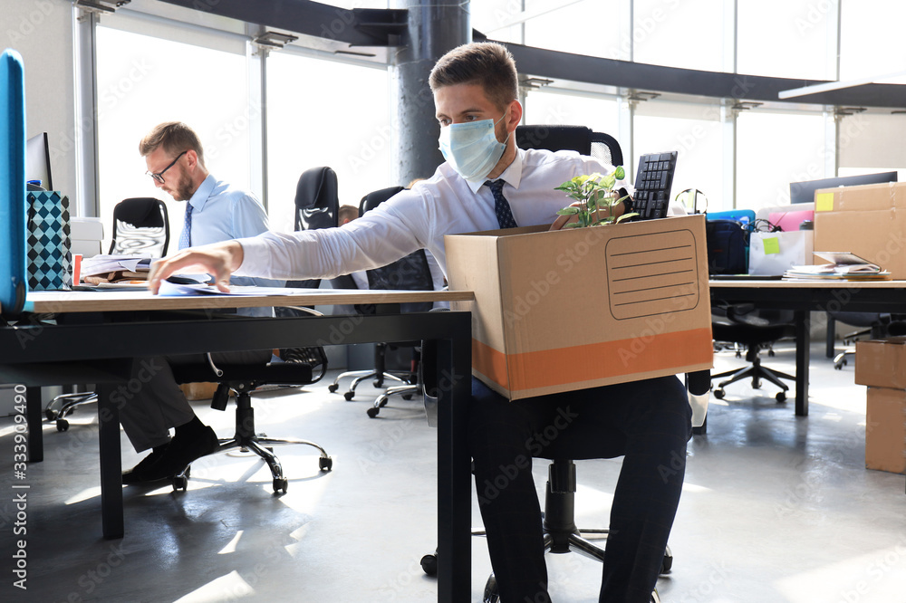Fototapeta Dismissal employee in an epidemic coronavirus. Sad dismissed worker are taking his office supplies with him from office.