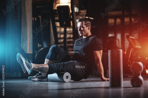 Fototapeta young man has crossfit workout with roller and weight in gym