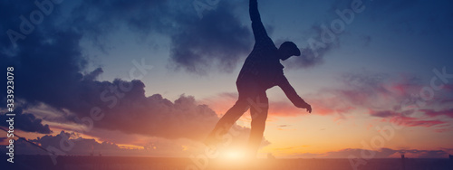 Fototapeta Silhouette of a young active man walking balance on top of the roof in the city at sunset. Wide screen panoramic obraz
