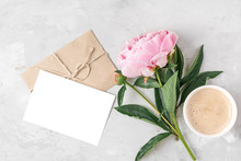 Morning Coffee Cup, Pink Peony Flower And Blank Greeting Card With Envelope On Light Background. Mock Up. Flat Lay