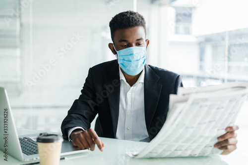 Fényképezés Handsome african businessman wear in medical mask with newspaper in the morning