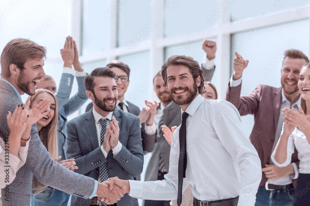 Fototapeta happy business team congratulating young business partners