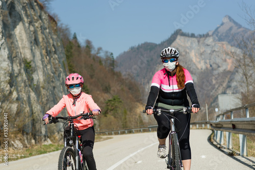 Fototapeta Mother and daughter biking and wearing medical mask obraz