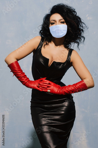 Valokuva Beautiful adult woman wearing in protection mask black spandex dress and long re