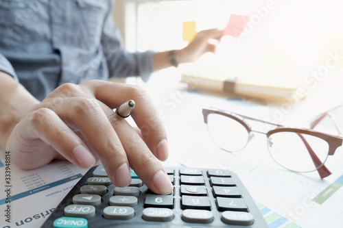 Fototapeta businessman or accountant hand working on calculator to calculate financial data report, accountancy document and laptop computer at office obraz