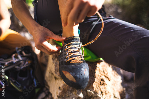 Obraz Rock climber puts on climbing shoes and ties shoelaces. - fototapety do salonu
