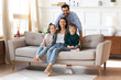 Portrait of smiling bearded father standing near couch with sitting happy wife and little children. Joyful affectionate family of four posing for photo, looking at camera, good relations concept.