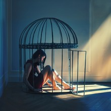 Young Woman Sitting In Cage