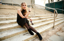 Photo Of A Fashionable Blonde Girl In A Black Dress Sitting In Various Poses On The Steps Of An Outdoor Building In The City In Spring