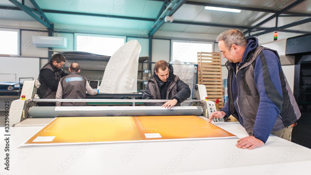 Obraz Large group of technicians works in printing printshop press hall fototapeta, plakat