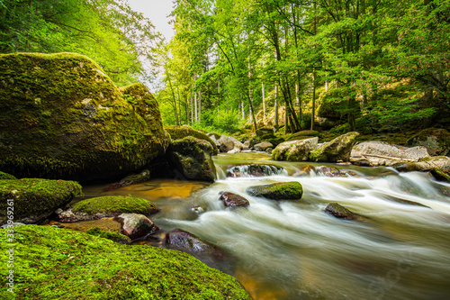 Fototapeta Beautiful river deep in the forest, sunny spring summer weather. Nature landscape, rocks and flowing water stream. Tranquil natural environment obraz