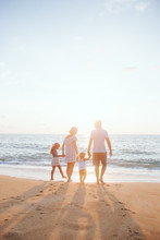 Holiday Travel Concept, Summer Vacations. Happy Family Are Having Fun On A Tropical Beach In Sunset.