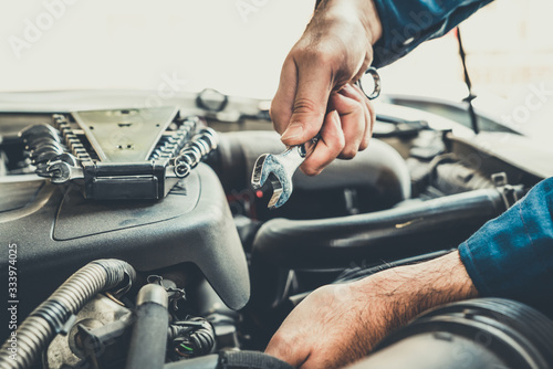 Fototapeta Professional mechanic providing car repair and maintenance service in auto garage. Car service business concept. obraz