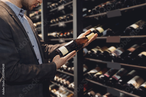 Sommelier man with wine bottle near rack store restaurant with exquisite drinks